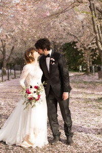 Bride & groom kissing beneath cherry blossoms