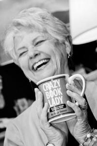Judith Briles laughing with a cup of coffee