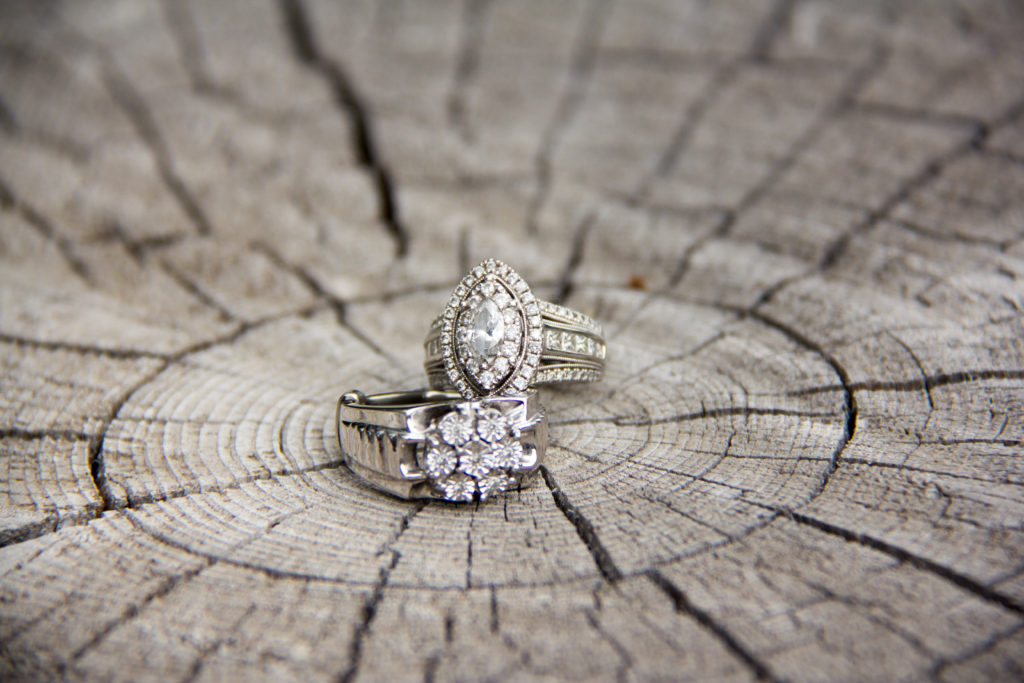sparkly wedding rings on cracked wooden log