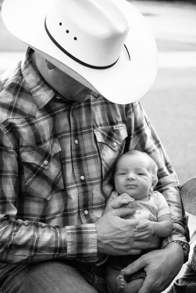 Cowboy holding baby
