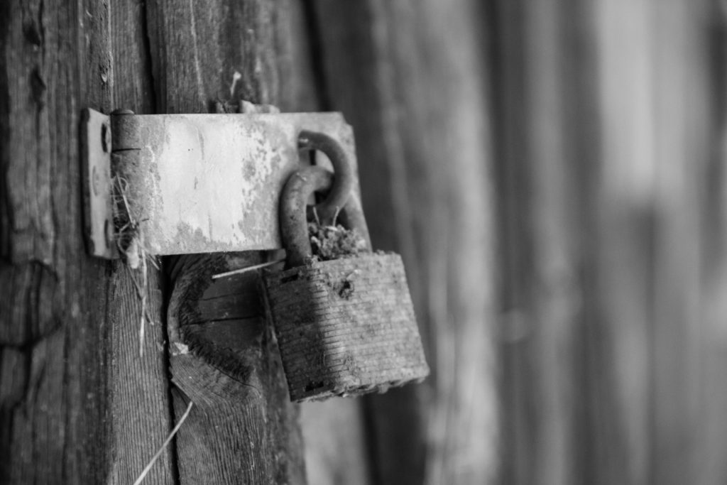 black and white pic of rusty lock on a barn door