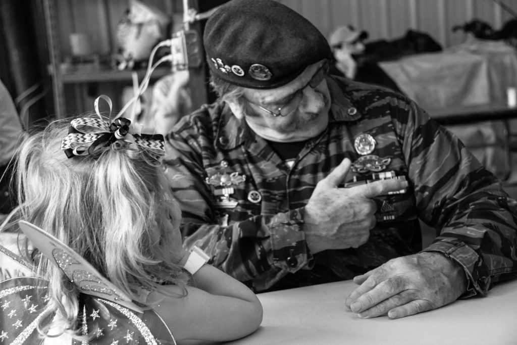 vietnam veteran showing his medals to a little girl