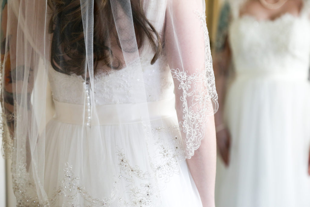bride looking at her veil in the mirror
