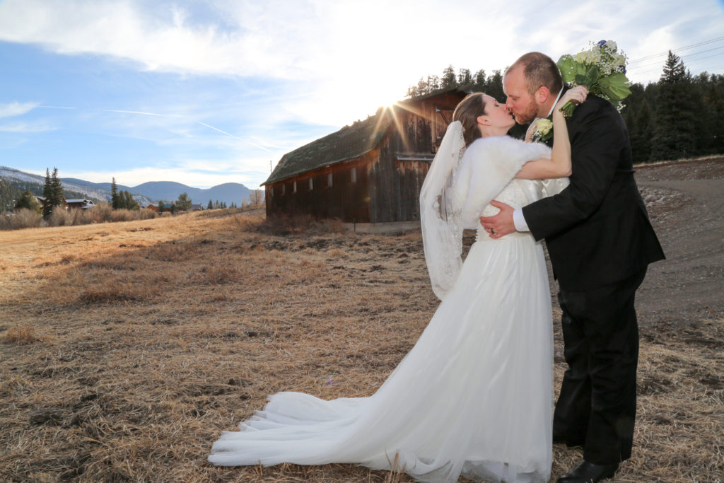 bride kissing groom by a barn at sunset
