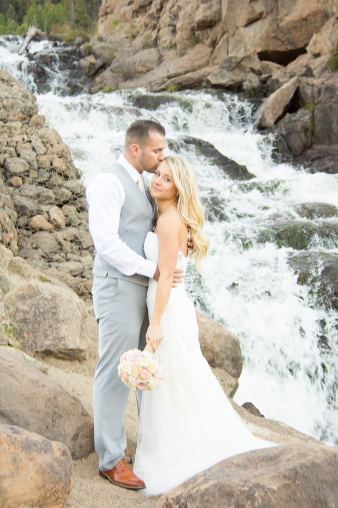 bide and groom kissing by waterfall in South Fork