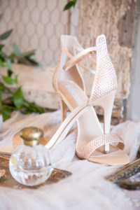 Champagne colored David Tutera high heels on a table next to a perfume bottle