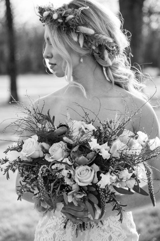 blond bohemian bride holding bouquet of flowers in the sunlight