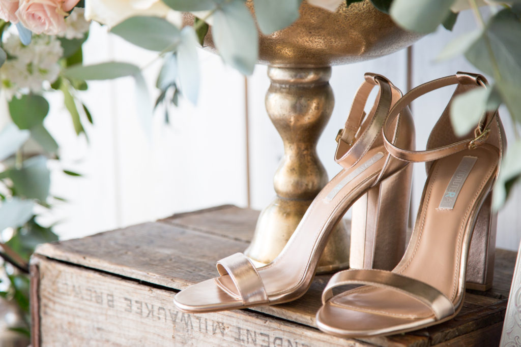 Rose gold high heels on wooden box next to flowers