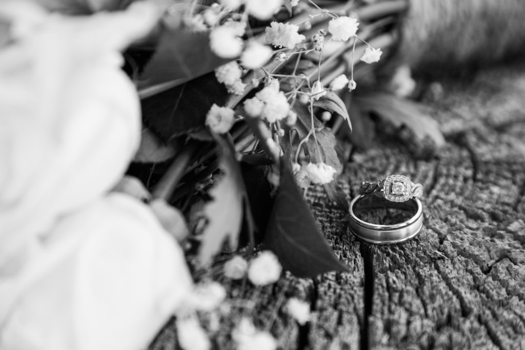 white roses sitting next to wedding rings on a wooden stump