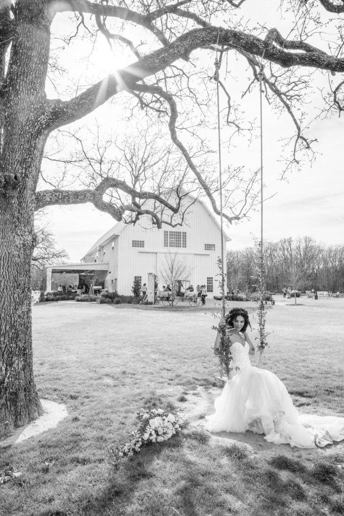 Beautiful bride swinging on a swing by White Sparrow Barn