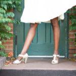 woman in front of ivy and green door in wedding heels