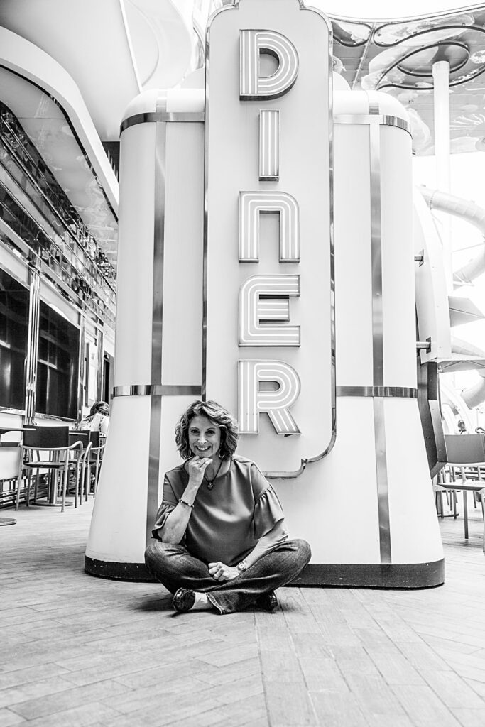Author L.A. Keller sitting cross legged in front o f a neon diner sign