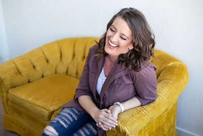 laughing photographer in a purple jacket sitting on a yellow couch