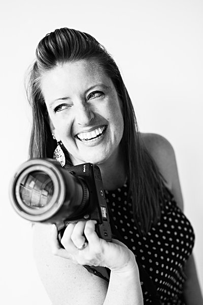 CO Photographer Ashlee Bratton with Ashography smiling with her camera