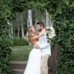 bride and groom snuggling in front of vine arbor