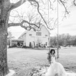 bride on swing in front of barn