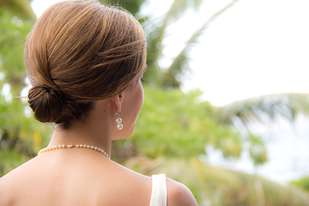 back of Hawaiian bride with pearl earrings looking at palm trees