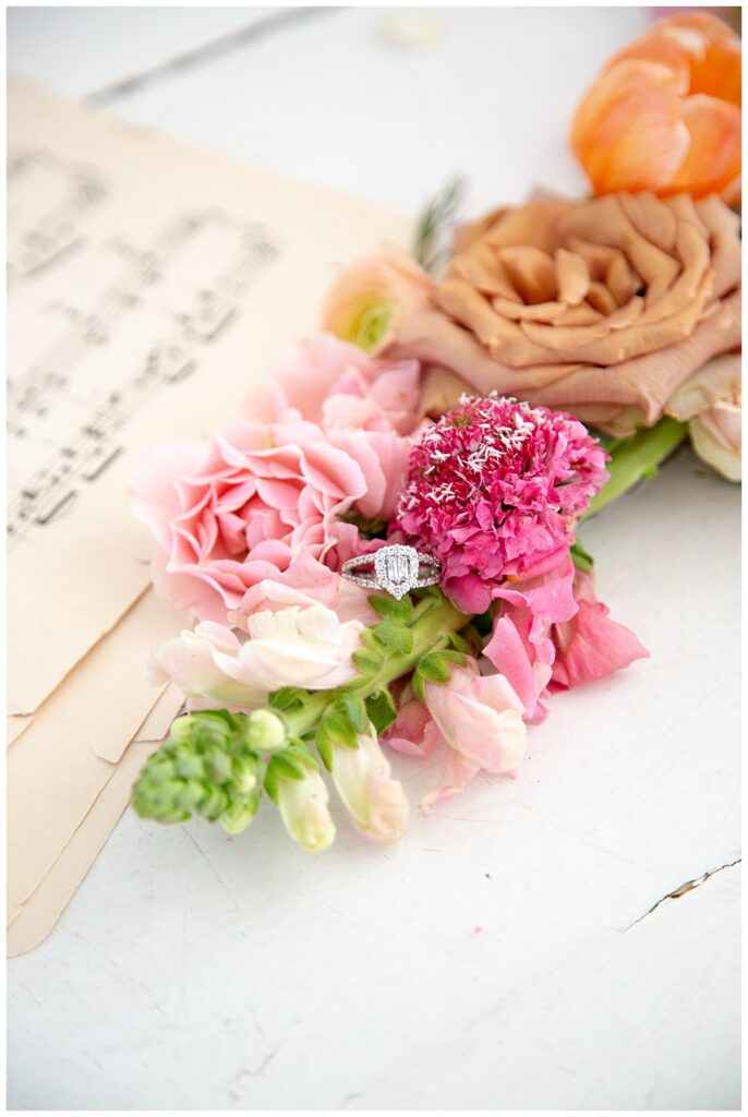 wedding ring in brightly colored flowers on top of music sheets
