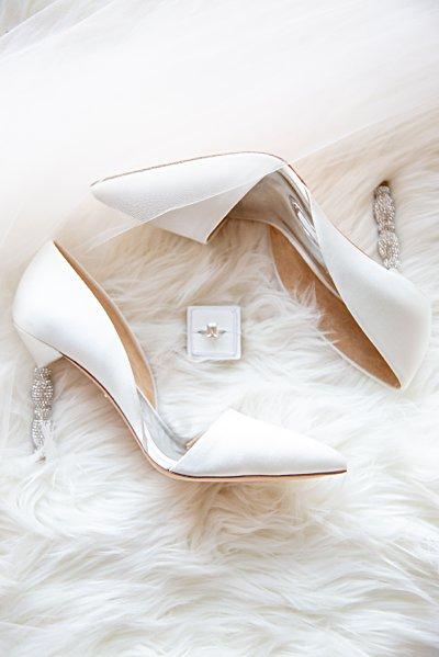 white wedding shoes surrounding wedding ring in ring box